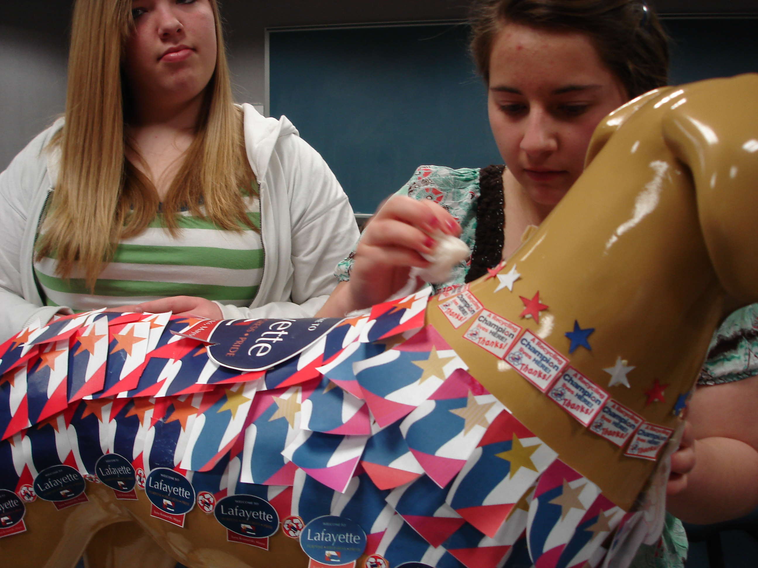 2 girls putting red, white and blue stickers on a plastic dog
