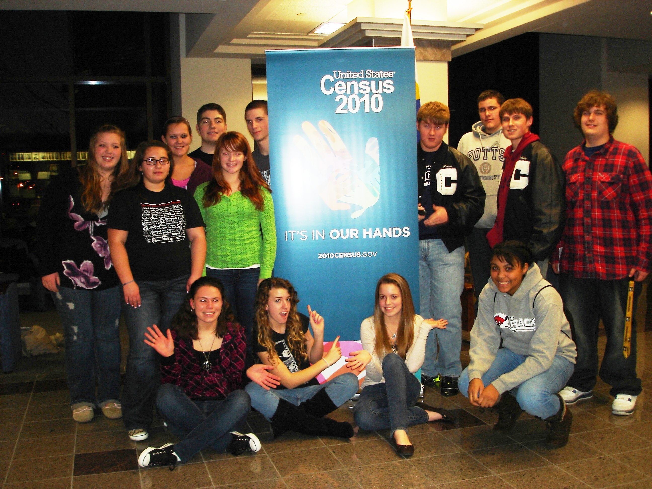 A group of teens in front of a 2010 Census banner