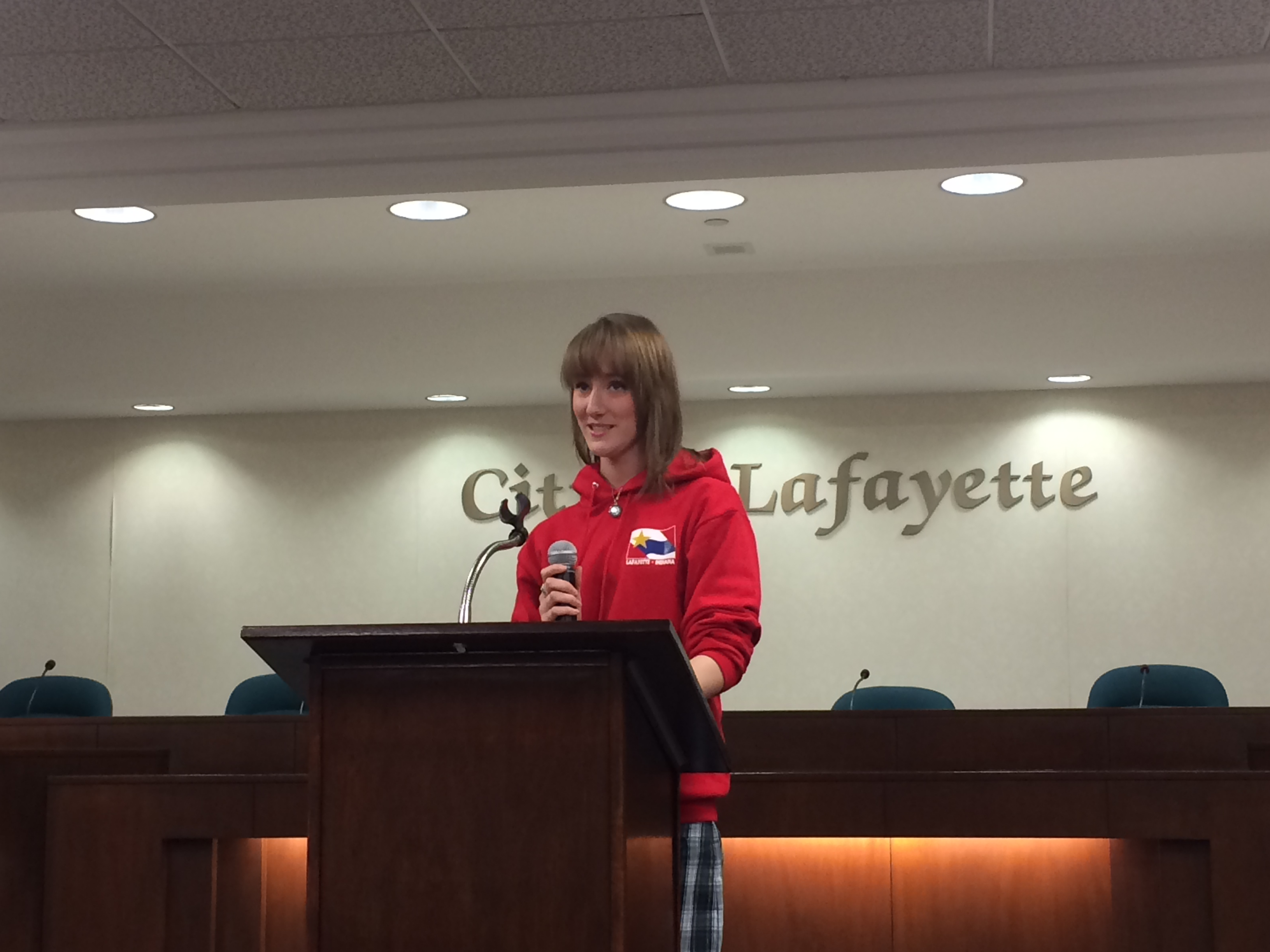 A teen girl in a red sweatshirt speaking at a podium
