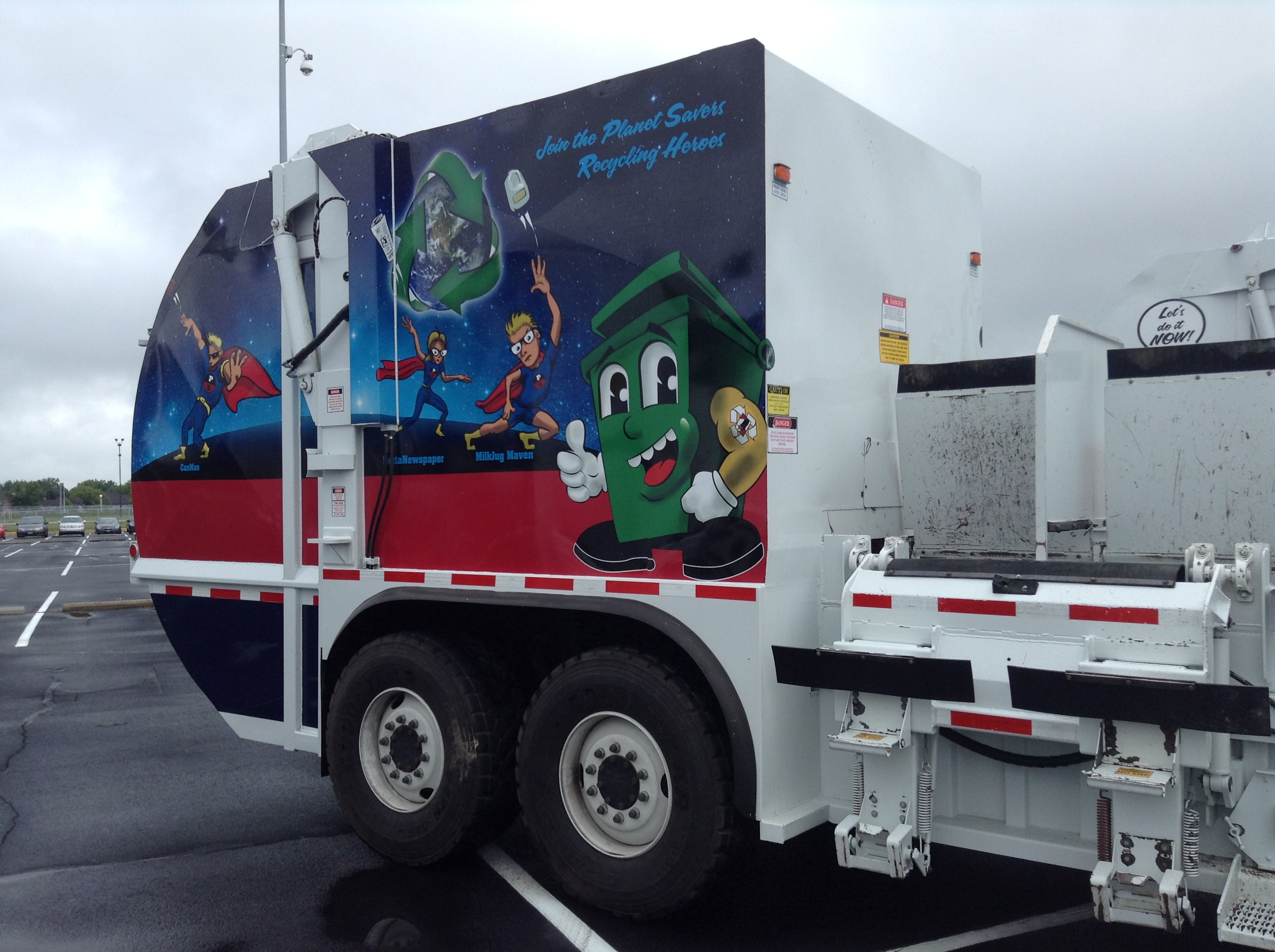 A trash truck with a cartoon dumpster on the side