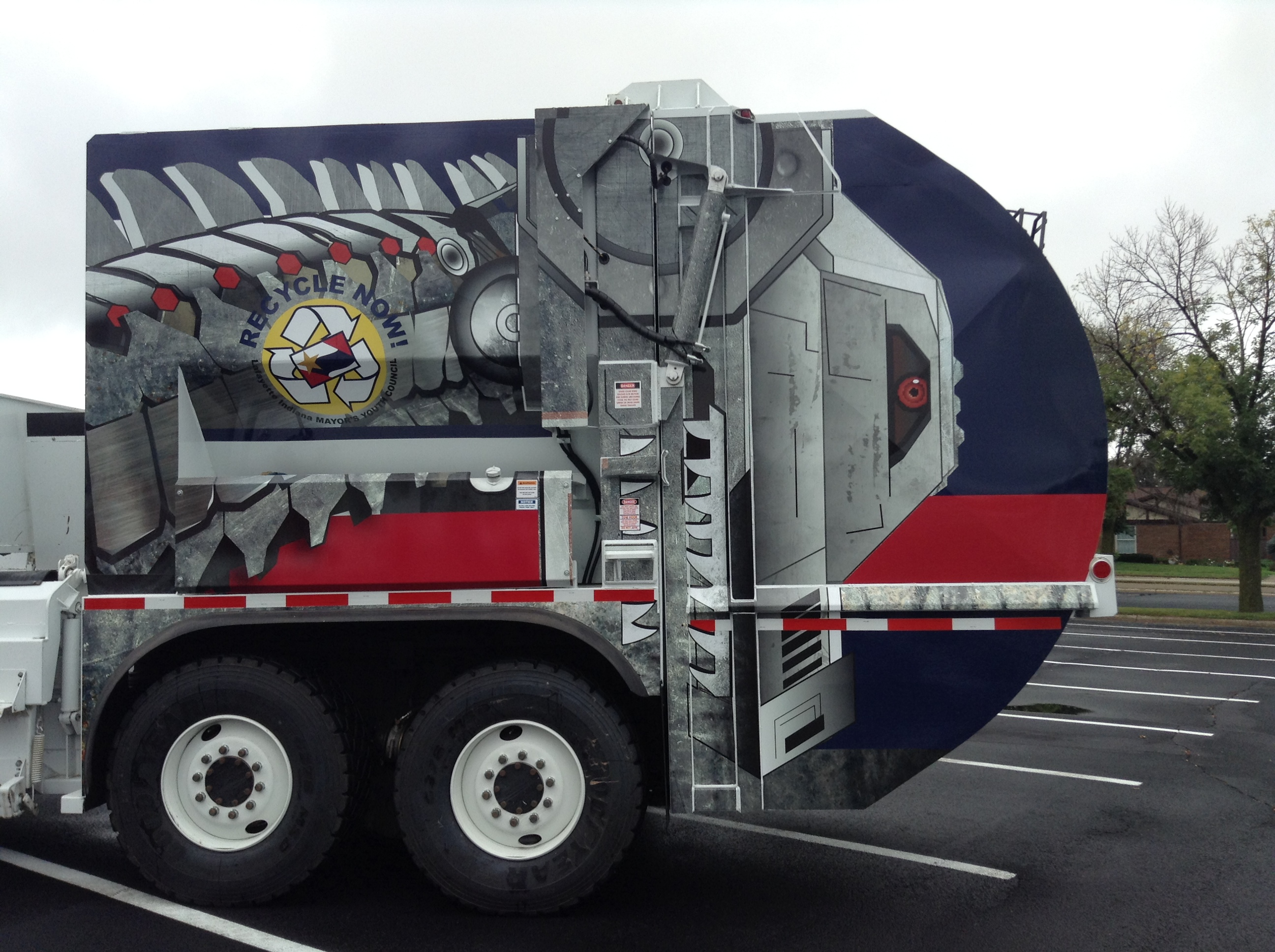 A trash truck with a robot mural on the side