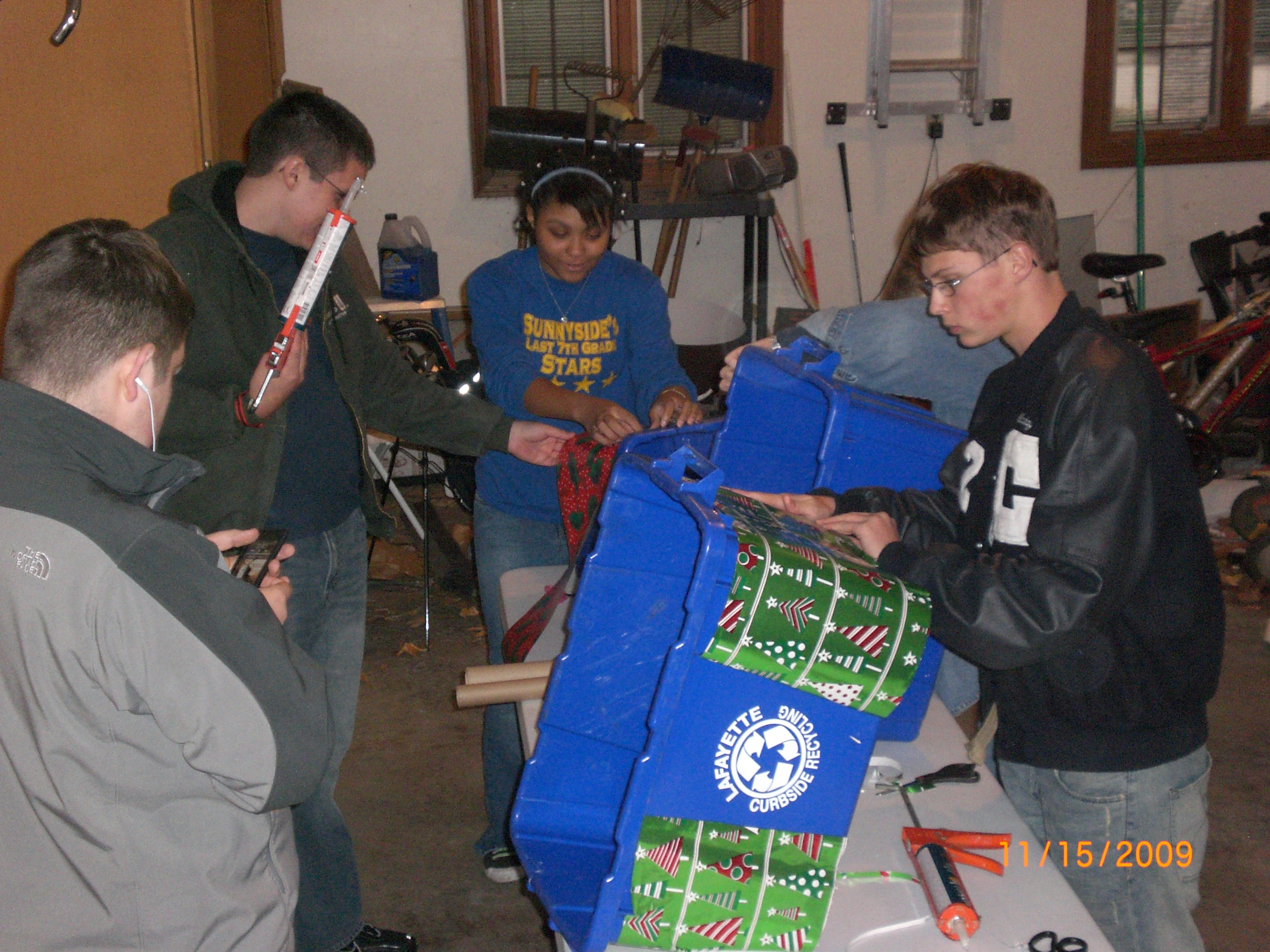 Teenagers preparing for the parade by decorating recycling bins