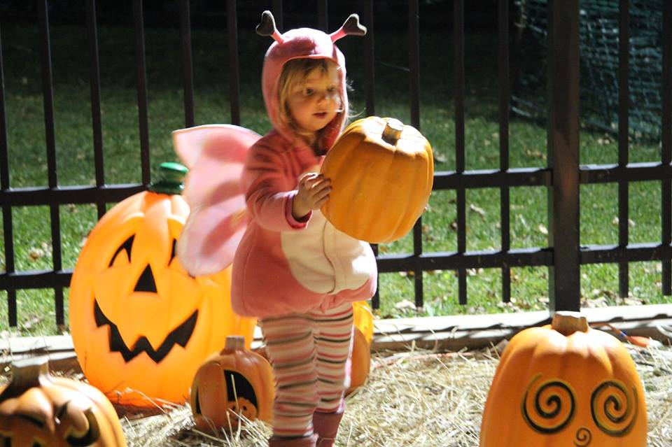 Girl in costume holding a pumpkin